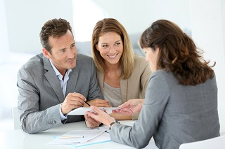 happy couple working with professional who is covered by commecial insurance