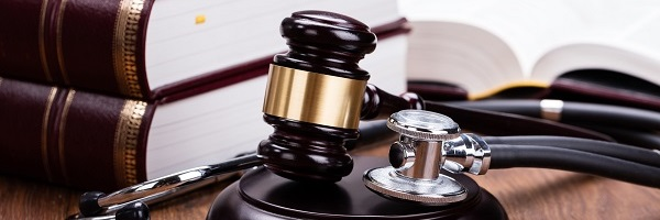 Gavel, stethoscope and law books representing underwriting rules of healthcare reform