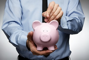 business man saving money in pink piggy bank to represent employer retirement plans